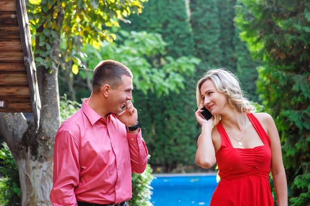 Jeune couple amoureux marchant dans le parc et parlant au téléphone