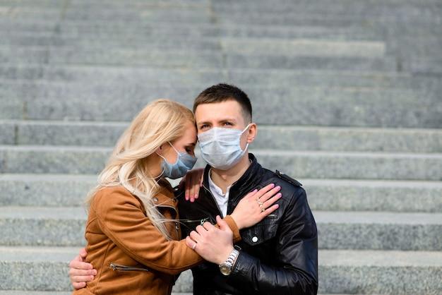 Jeune couple amoureux en masque médical de protection sur le visage en plein air dans la rue. concept de pollution de l'environnement. guy et fille en protection antivirus
