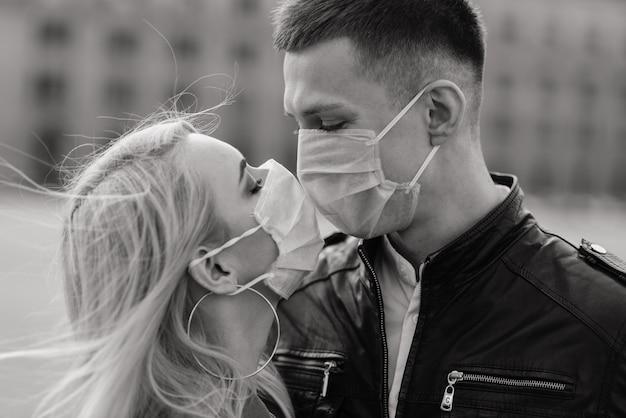 Jeune couple amoureux en masque médical de protection sur le visage en plein air dans la rue. conception de la protection covid.