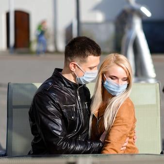 Jeune couple amoureux en masque médical de protection sur le visage en plein air dans la rue. guy et fille dans la protection contre les virus.