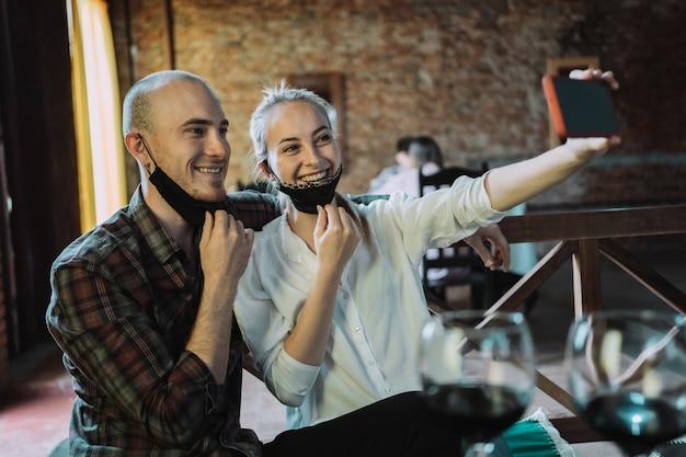 Jeune couple amoureux de masques ouverts prenant selfie dans un restaurant
