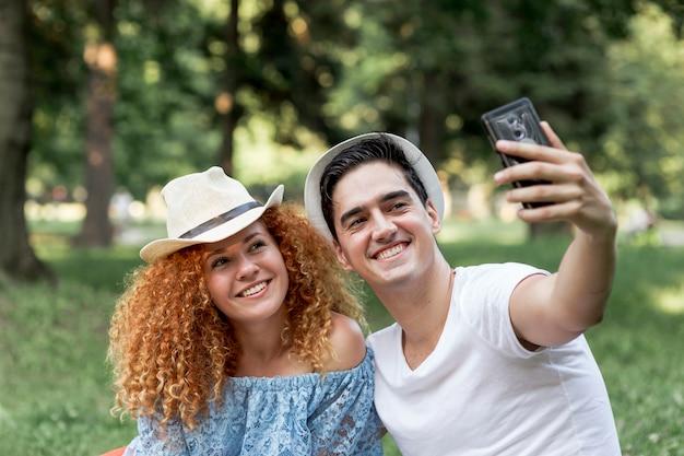 Jeune couple d'amoureux en plein air prenant un selfie