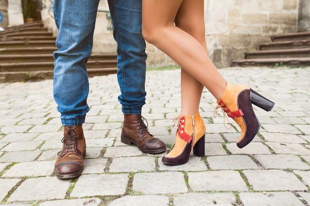 Jeune couple amoureux posant dans la vieille ville, recadrée sur pieds