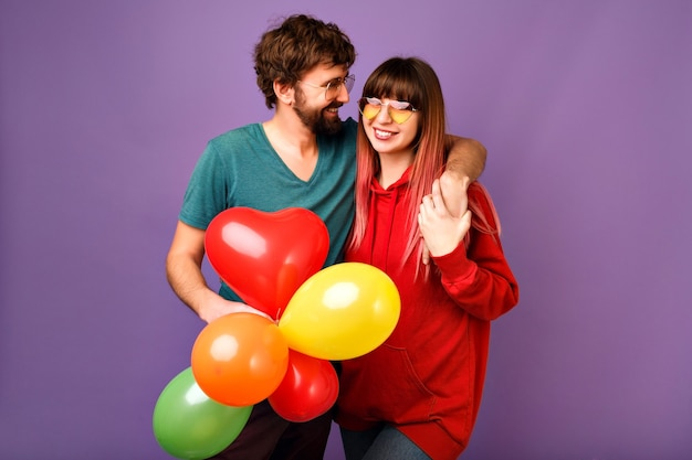 Jeune couple amoureux posant sur mur violet avec des ballons