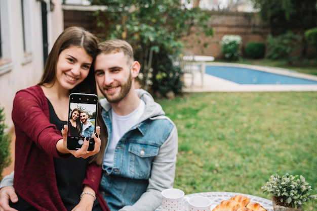 Jeune couple amoureux prenant selfie dans le jardin