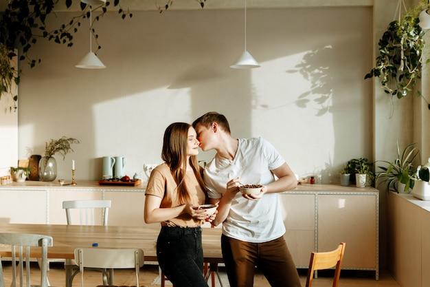 Un jeune couple amoureux prend le petit déjeuner ensemble à la maison dans la cuisine. homme et femme mangeant des céréales avec du lait pour le petit déjeuner.