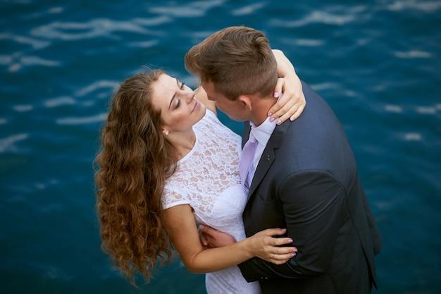 Jeune couple d'amoureux en promenade au bord du lac le jour de leur mariage.