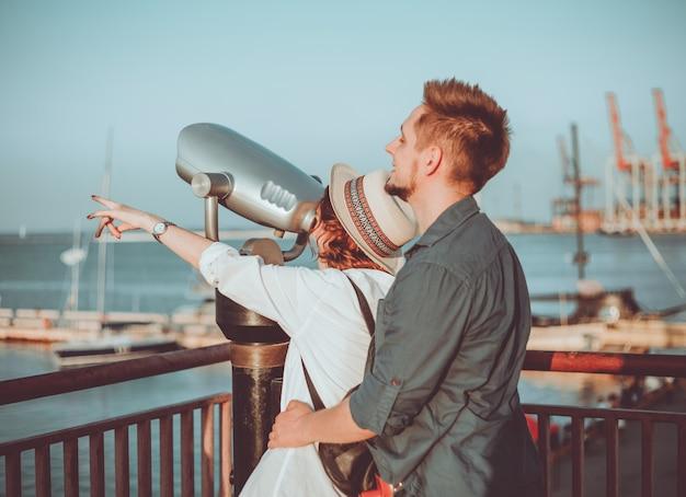 Jeune couple amoureux regarde à travers les jumelles de la ville à la station maritime.