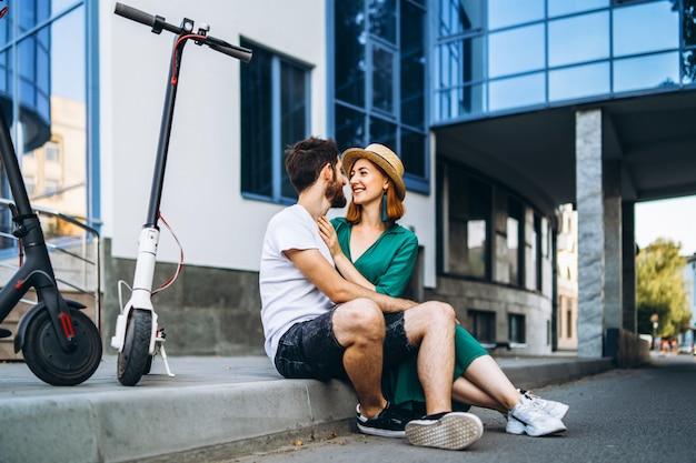 Jeune couple d'amoureux relaxant assis près d'un bâtiment en verre moderne avec leurs scooters électriques.