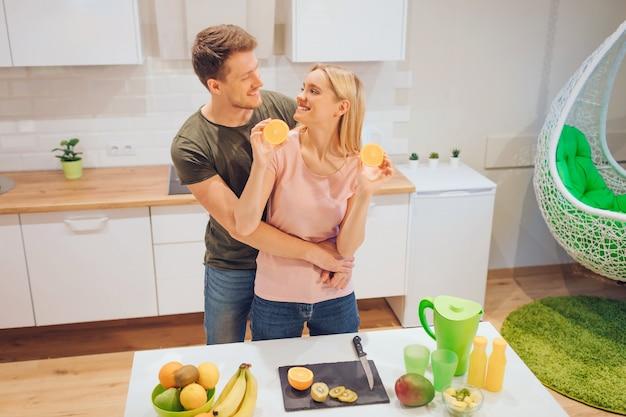 Un jeune couple d'amoureux s'amuse avec de l'orange biologique tout en cuisinant des fruits frais dans une cuisine blanche. nourriture saine. famille heureuse. alimentation équilibrée