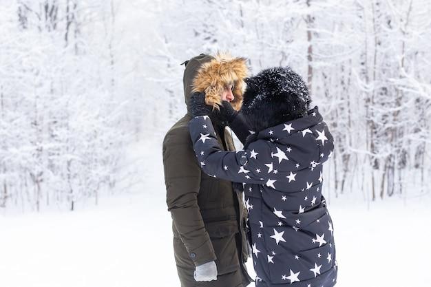 Jeune couple amoureux s'amuser dans la forêt enneigée. vacances d'hiver actives.