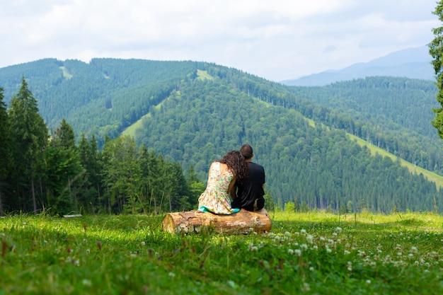 Un jeune couple amoureux s'embrasse assis sur la bûche et profite de la nature overgrov du paysage de montagne avec des arbres verts.