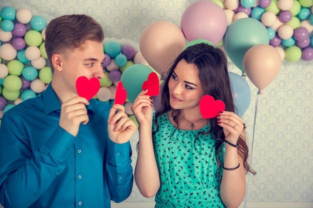 Jeune couple amoureux s'embrassent, se couvrent les lèvres avec un bonbon en forme de coeur