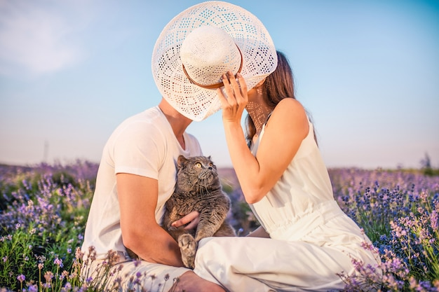 Jeune couple amoureux s'embrasser se couvrant d'un chapeau de paille.