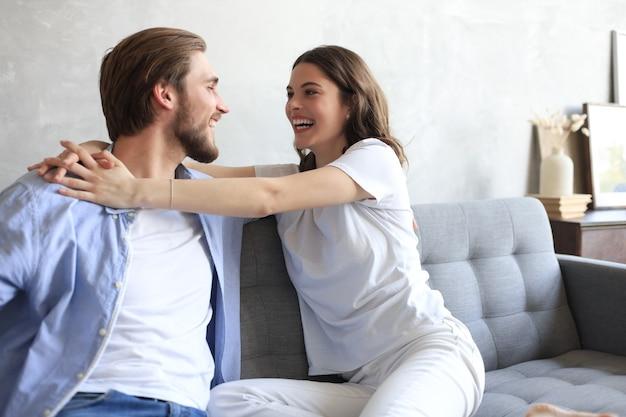 Jeune couple d'amoureux se détendre sur le canapé ensemble. la femme et l'homme s'embrassent et profitent de la compagnie l'un de l'autre assis sur un canapé, main dans la main, ayant un rendez-vous romantique.