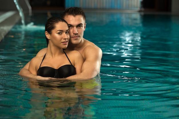 Jeune couple d'amoureux se détendre dans la piscine spa ensemble