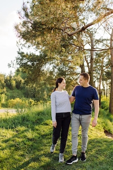Un jeune couple amoureux se promène dans les bois, s'amusant ensemble