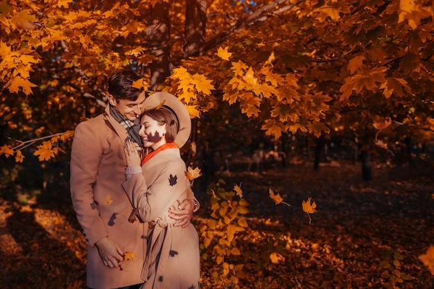 Jeune couple amoureux se promène dans la forêt d'automne parmi les feuilles qui tombent