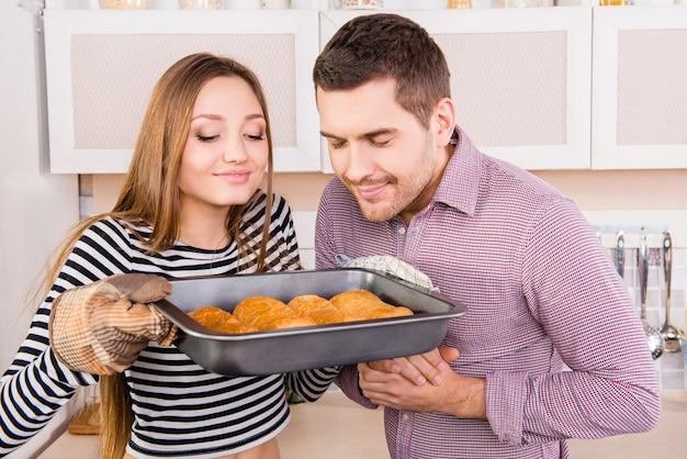 Jeune couple amoureux sentant des gâteaux cuits au four dans la cuisine