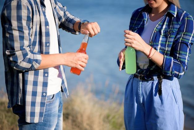 Jeune couple amoureux en sirotant un cocktail à la plage.
