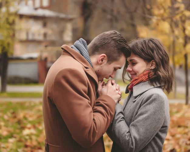 Jeune couple amoureux tenant par la main et se promener dans un parc sur une journée ensoleillée d'automne