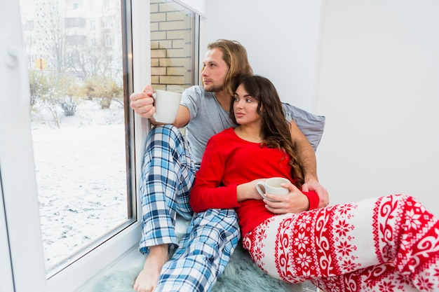 Jeune couple d'amoureux tenant une tasse de café assis sur le rebord de la fenêtre