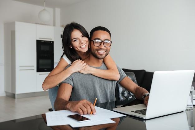 Jeune couple d'amoureux utilisant un ordinateur portable et analysant leurs finances. en regardant devant.