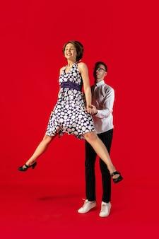Jeune couple à l'ancienne danse isolé sur fond rouge