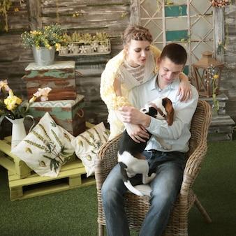 Jeune couple avec animal assis sur une chaise dans le salon.