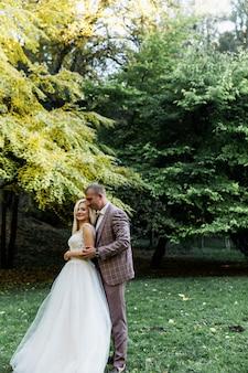Jeune couple appréciant des moments romantiques en marchant dans le parc. élégante mariée et le marié posant et s'embrassant dans le parc le jour de leur mariage. mariée élégante dans une belle robe blanche, marié en costume.