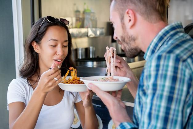 Jeune couple, apprécier, manger, pâtes, depuis, camion nourriture