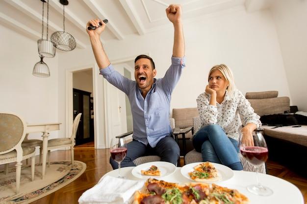 Jeune couple, apprécier, manger pizza, et, regarder télé