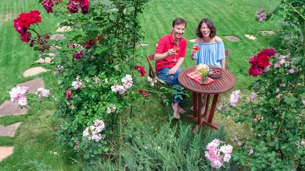 Jeune couple, apprécier, nourriture, et, vin, dans, beau, roses, jardin, sur, romantique, date, aérien, vue dessus, au-dessus, de, homme femme, manger, et, boire, ensemble, dehors, dans parc
