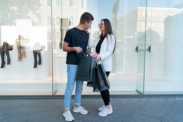 Jeune couple après des achats réussis. guy et fille sur fond de vitrine.