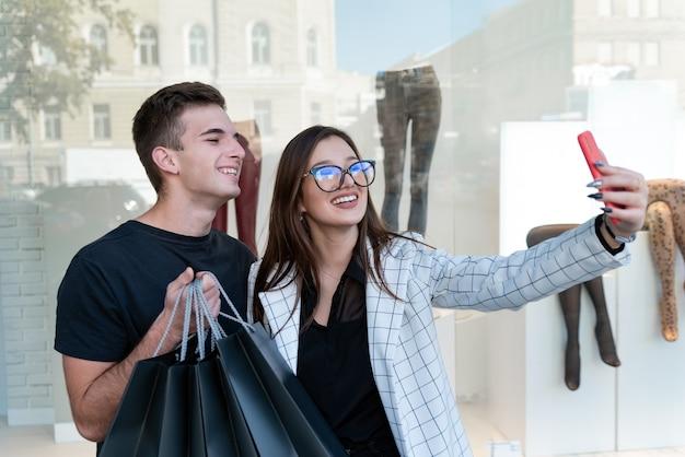 Jeune couple après le shopping fait selfie. fille se photographie elle-même et son petit ami.