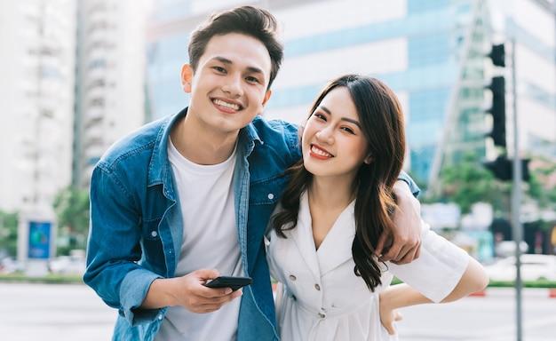 Jeune couple asiatique à l'aide de smartphone ensemble dans la rue