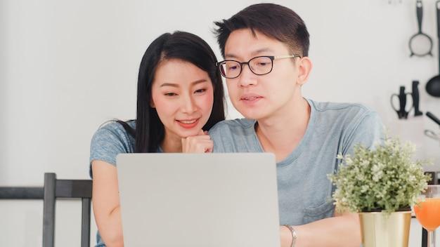 Jeune couple asiatique aime faire du shopping en ligne sur un ordinateur portable à la maison. mode de vie jeune mari et femme heureuse acheter un commerce électronique après le petit déjeuner dans la cuisine moderne à la maison le matin.