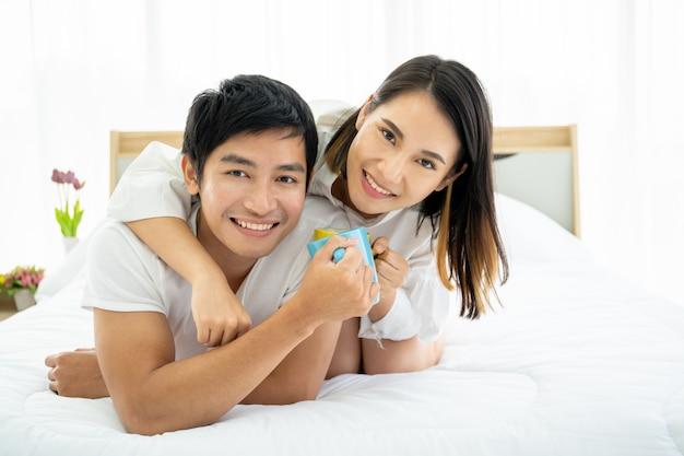 Jeune couple asiatique appréciant avec café le matin dans la mauvaise chambre, les loisirs, le couple, la relation et la saint-valentin. photographie avec fond.