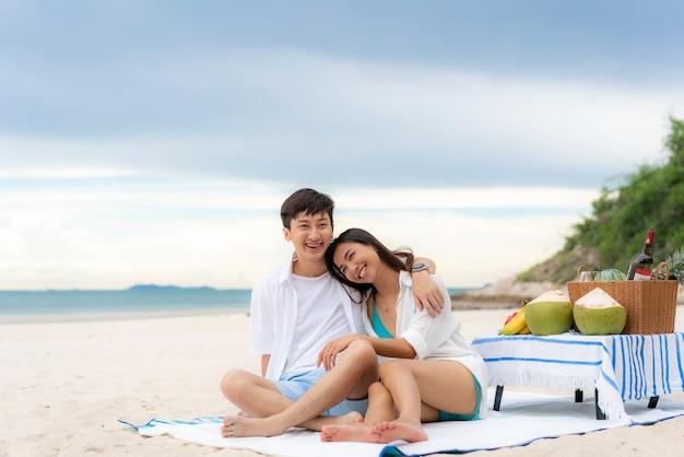 Jeune couple asiatique assis sur la couverture de pique-nique à la plage