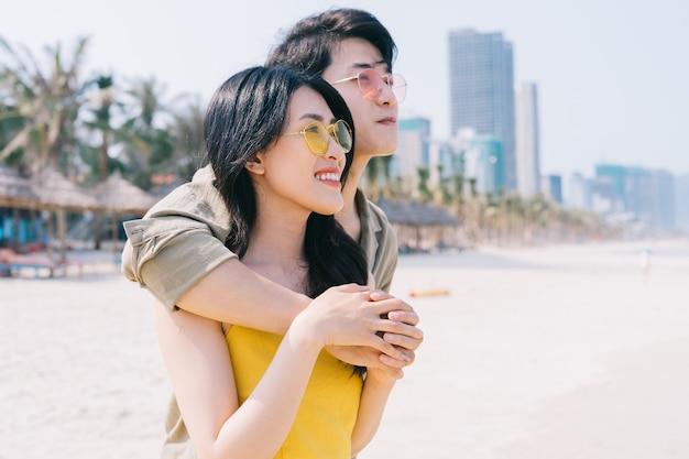 Jeune couple asiatique bénéficiant de vacances d'été sur la plage