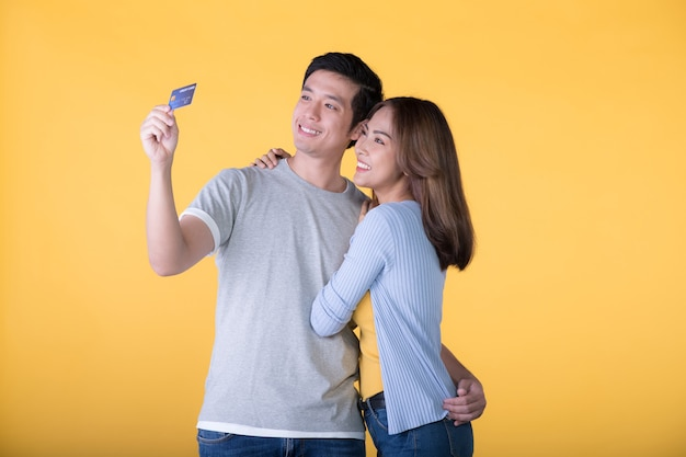 Jeune couple asiatique avec carte de crédit isolé sur mur jaune
