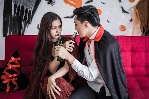 Jeune couple asiatique en costume de sorcière et dracula avec célébrer la fête d'halloween et boire de la bière ensemble au festival d'halloween dans la chambre à la maison. les couples de concept célèbrent halloween ensemble à la maison.