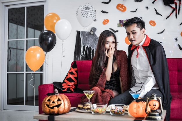 Jeune couple asiatique en costume de sorcière et dracula avec célébrer la fête d'halloween et boire du vin ensemble au festival d'halloween sur un canapé rouge dans la chambre à la maison.