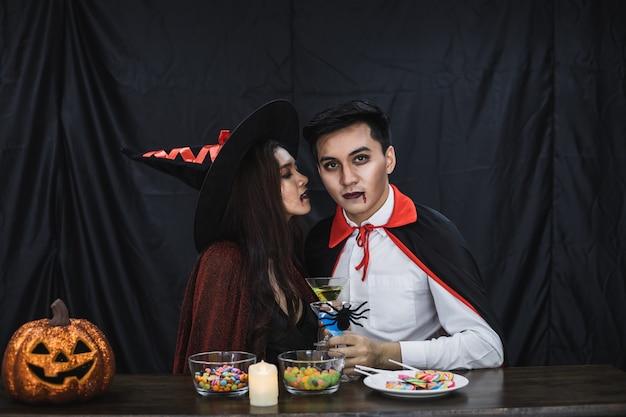 Jeune couple asiatique en costume de sorcière et dracula avec célébrer la fête d'halloween pour un verre à trinquer et boire au festival d'halloween. un couple en costume célèbre le fond de tissu noir de la fête d'halloween.