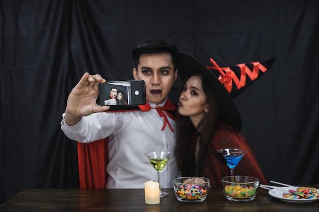 Jeune couple asiatique en costume de sorcière et dracula avec selfie par mobile pour célébrer la fête d'halloween. un couple en costume célèbre le fond de tissu noir de la fête d'halloween.