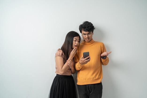 Jeune couple asiatique debout en regardant l'écran d'un téléphone intelligent expression de surprise
