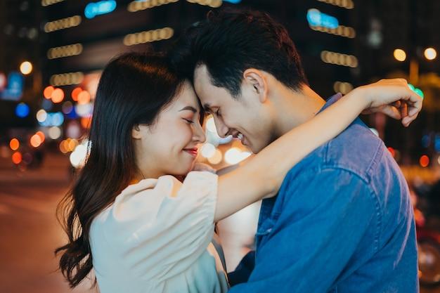 Jeune couple asiatique embrassant ensemble dans la rue pendant la nuit