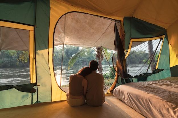 Jeune couple asiatique embrassant et relaxant à l'intérieur d'une tente