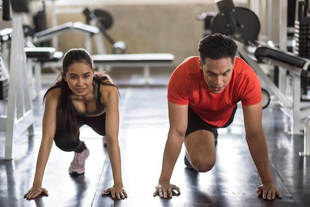 Jeune couple asiatique étirant les jambes et les pieds pour se réchauffer avant de faire de l'exercice dans une salle de sport. musculation sportive et concept de mode de vie sain.