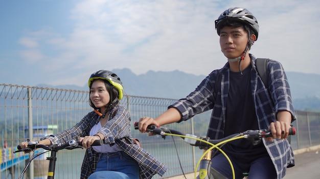 Un jeune couple asiatique fait du vélo ensemble pour aller travailler